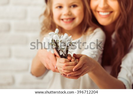 Beautiful young mother and her cute daughter are looking at camera and smiling. Little girl is holding flowers, close up - stock photo