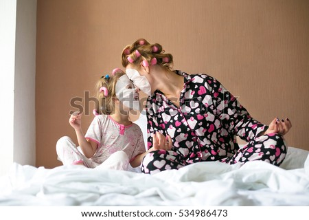 Beautiful young mother and her cute daughter in pajamas and with hair curlers on heads  Mother and her daughter child girl playing and hugging.