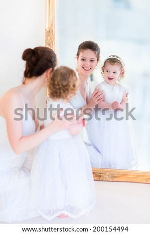 Beautiful young mother and her cute little daughter, adorable toddler girl with curly hair wearing a white bridesmaid dress playing next to a big mirror watching reflection and laughing - stock photo