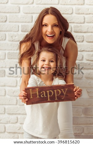 Beautiful young mother and her cute little daughter are holding a wooden plate Happy, looking at camera and smiling, against white brick wall - stock photo