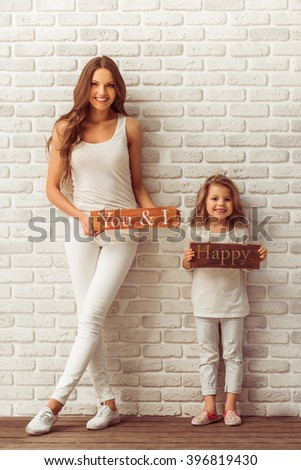 Beautiful young mother and her cute little daughter are holding wooden plates, looking at camera and smiling, against white brick wall - stock photo