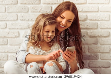 Beautiful young mother and her cute little daughter are listening to music using a smart phone and smiling, against white brick wall - stock photo