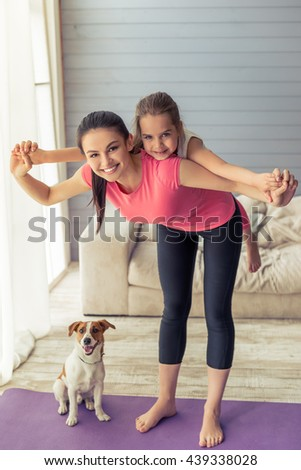 Beautiful young mother and her cute little daughter are looking at camera and smiling while doing yoga at home, their dog is near - stock photo