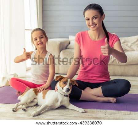 Beautiful young mother and her cute little daughter are showing Ok sign and smiling while sitting in with their dog on yoga mat at home - stock photo