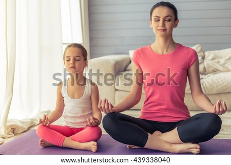 Beautiful young mother and her cute little daughter are smiling and meditating while sitting in lotus pose on yoga mat at home - stock photo