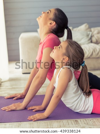 Beautiful young mother and her cute little daughter are smiling while stretching on yoga mat at home - stock photo