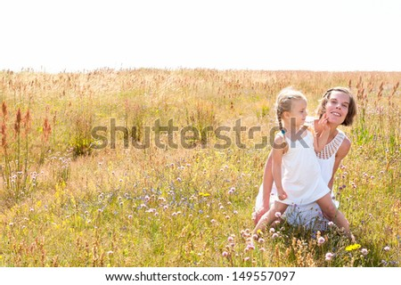 Beautiful young mother and her cute little daughter dressed in white summer dresses, sitting on a meadow with wild flowers on a warm summer day. Copy space in the sky area.