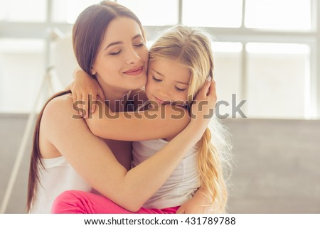 Beautiful young mother and her daughter are hugging and smiling while sitting with closed eyes on the bed at home - stock photo
