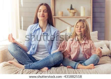 Beautiful young mother and her daughter are meditating and smiling while sitting in yoga pose on the sofa at home - stock photo