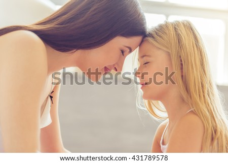 Beautiful young mother and her daughter are smiling while sitting together head to head - stock photo