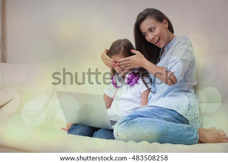 Beautiful young mother and her daughter are using gadgets and smiling while sitting on the sofa at home