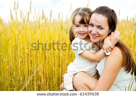 beautiful young mother and her daughter having fun at the wheat field - stock photo