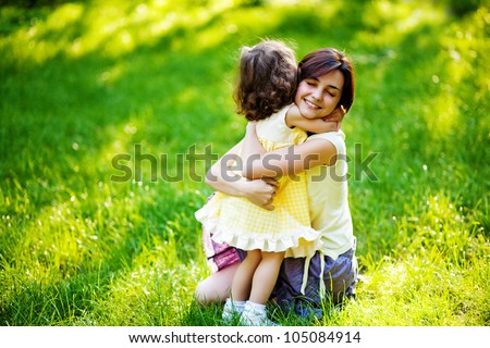 beautiful young mother and her daughter having fun on the green grass