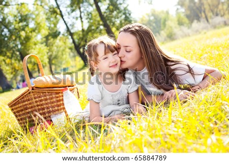 beautiful young mother and her daughter having picnic in the park on a sunny day - stock photo