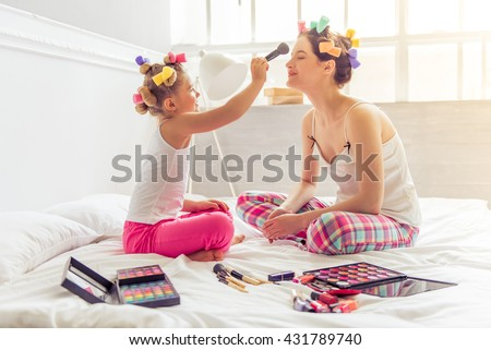 Beautiful young mother and her daughter in pajamas and with hair curlers on bed at home. Cute little girl is doing her mother makeup - stock photo