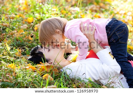 beautiful young mother and her daughter lying on the autumn leaves