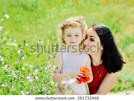 beautiful young mother and her daughter relaxing in field - stock photo