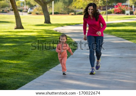 Beautiful young mother and her daughter running in the neighborhood.  They are on a sidewalk in a grassy greenbelt.  The mother is playfully chasing her daughter. - stock photo