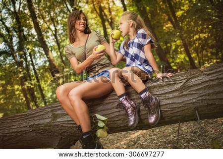 Beautiful young mother and her daughter sitting on fallen tree in the forest and enjoying. They looking at each other and eat apples.