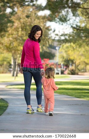 Beautiful young mother and her daughter walking in the neighborhood.  They are on a sidewalk in a grassy greenbelt.  They are holding hands. - stock photo