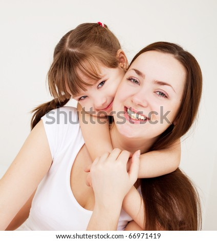 beautiful young mother and her five year old daughter at home