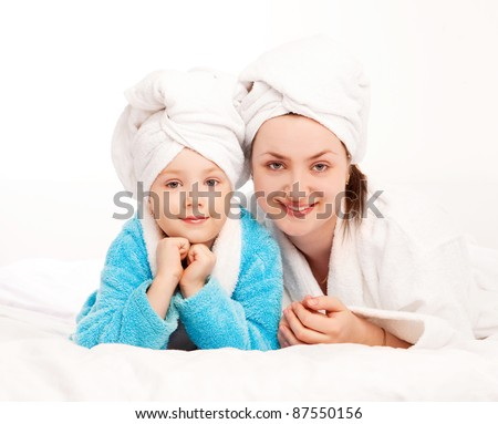 beautiful young mother and her five year old daughter on the bed at home - stock photo
