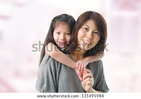 Beautiful young mother and her five years old daughter at home. Happy Asian parent and child. - stock photo