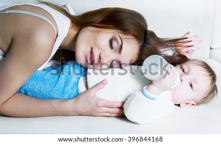 beautiful young mother and her one year old baby at home - stock photo