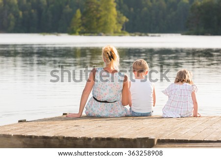 Beautiful young mother and her two kids sitting on a jetty in the summer sun, bathe the feet in the water, and enjoy a beautiful day in midsummer. - stock photo