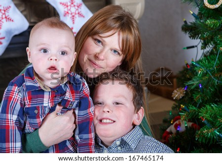 Beautiful young mother and two adorable sibling boys with Christmas tree and decoration.