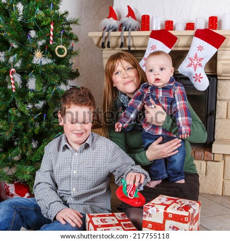 Beautiful young mother and two adorable sibling boys with Christmas tree and decoration. Square format. - stock photo