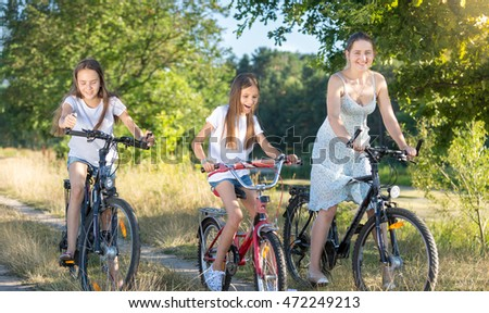 Beautiful young mother cycling with two daughters at meadow