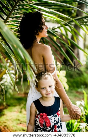 beautiful young mother daughter relaxing sitting grass background summer meadow green grass trees - stock photo