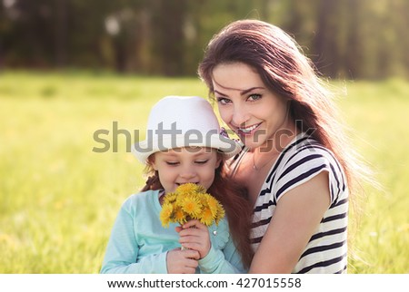 Beautiful young mother embracing her cute daughter with yellow bright flowers on summer background - stock photo
