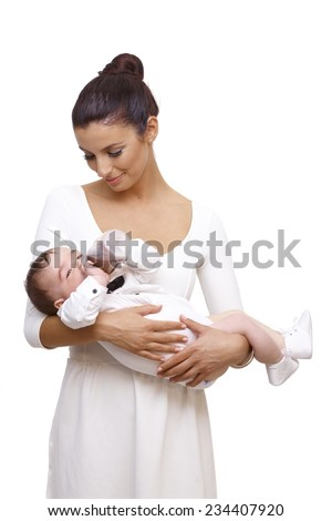 Beautiful young mother holding baby boy in arm. Baby drinking from feeding bottle, wearing bow tie and shirt. - stock photo
