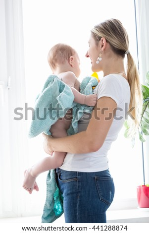 Beautiful young mother holding her baby boy covered in blue towel after bathing at big window - stock photo