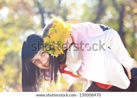 beautiful young mother holding her daughter in a wreath of maple leaves on back