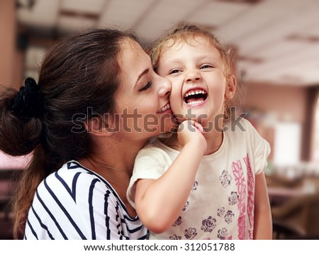 Beautiful young mother hugging her joying happy daughter indoor background