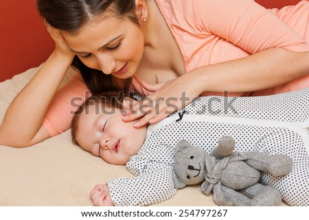 Beautiful young mother in bed with her sleeping baby.