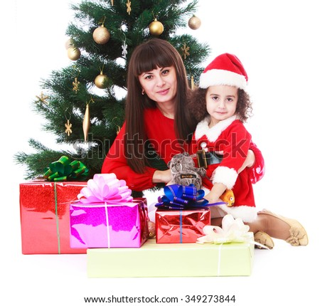 Beautiful young mother in the arms of his beloved little daughter in the background of Christmas gifts and a Christmas tree. Girl dressed costume hat Santa Claus - Isolated on white background.The