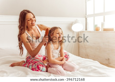 Beautiful young mother is combing her cute little daughter hair. Both in pajamas sitting on bed and smiling - stock photo