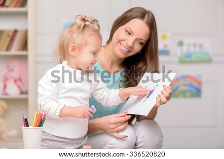 Beautiful young mother is holding a picture of the family is showing it to her daughter. The girl is pointing finger at the paper. She is holding the paint and smiling - stock photo