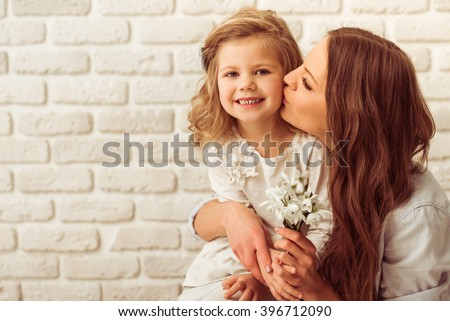 Beautiful young mother is holding flowers and kissing her cute little daughter, against white brick wall. Little girl is smiling - stock photo