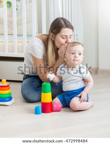 Beautiful young mother kissing her baby boy playing on on floor with colorful blocks