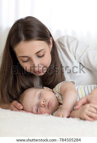 Beautiful young mother looks at her 7 months old baby sleeping in the bed