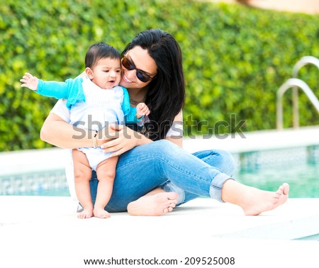 beautiful young mother playing with baby boy near the swimming pool on a sunny  day - stock photo