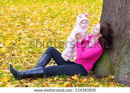 Beautiful young mother playing with her cute little baby daughter sitting on yellow autumn leaves under a big old tree in a sunny fall park - stock photo