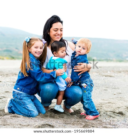 beautiful young mother playing with her kids on the beach on a sunny summer day - stock photo