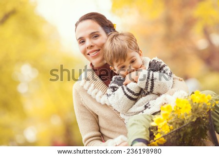 Beautiful young mother riding a bicycle with her cute little son sitting on the handlebars - stock photo