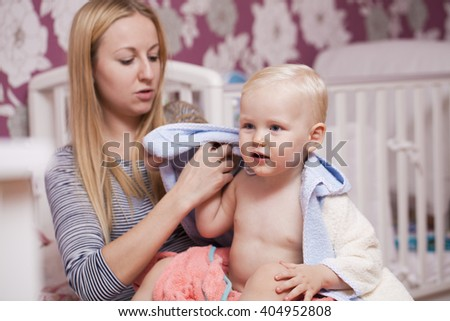 Beautiful young mother with adorable baby boy at home - stock photo